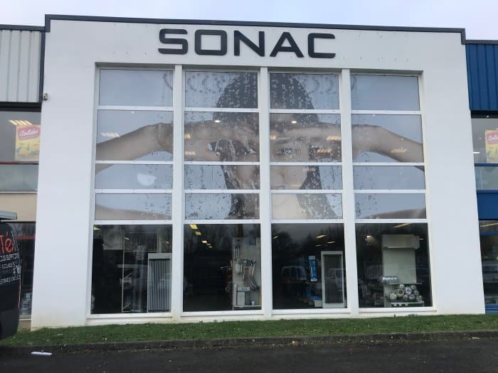 impact communication réalisation de décoration de vitrine avec adhésif micro-perforé pour le magasin Sonac à Rennes (35)