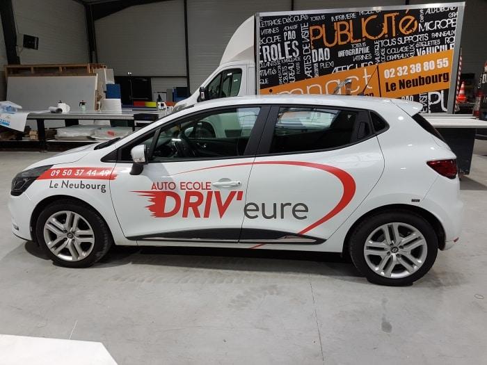 Impact communication réalisation et pose d'une publicité sur voiture renault clio 4 pour l'auto école Driv'Eure situé au Neubourg